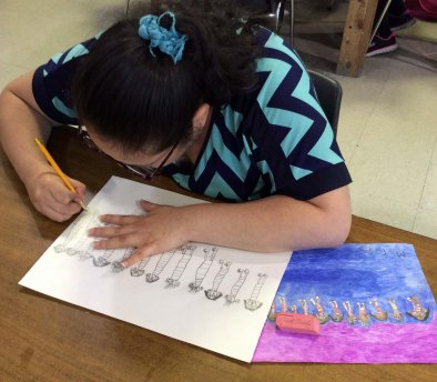 EC artist Martha Rojas is working on a row of figures, with her completed sketch to her left.